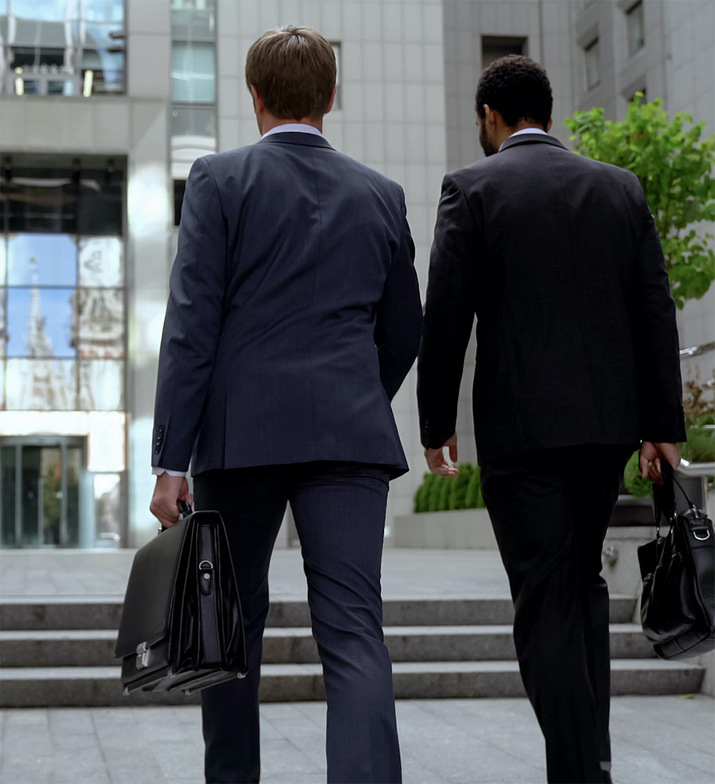 two men in business suits holding brief caseswalking together away from the camera towards a large building in the background