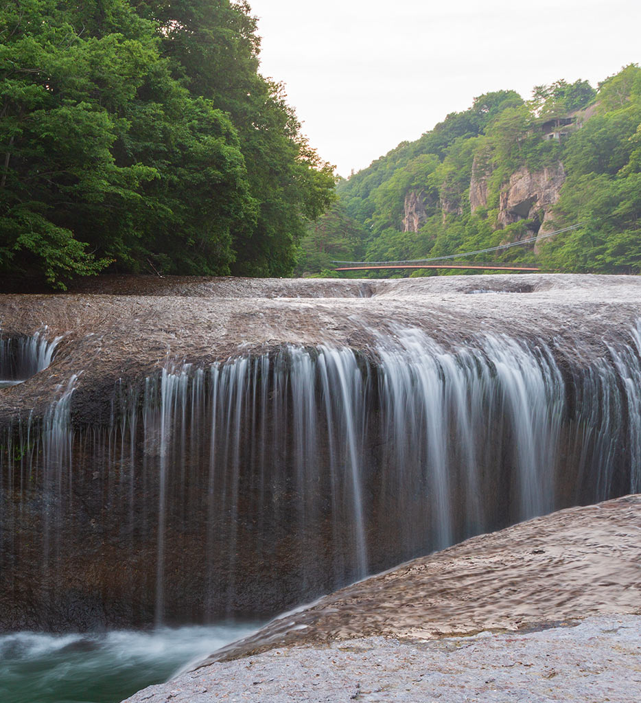 an image of a river with a small waterfall with lots of green trees and plants in the background